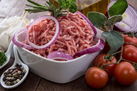 carne macinata: Ciotola con carne macinata su fondo in legno