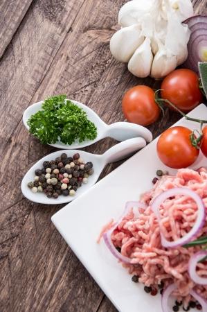 carne macinata: Piastra con porzione di carne macinata su sfondo di legno