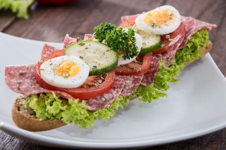 Fresh made Salami Sandwich on wooden background photo