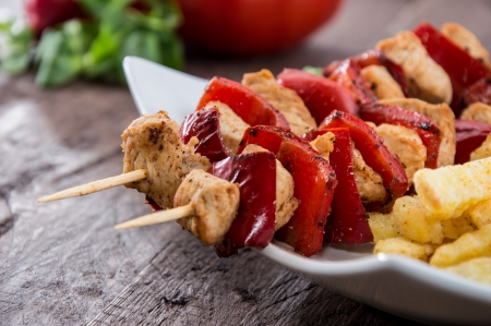 Fresh Skewer with french fries on wooden background photo