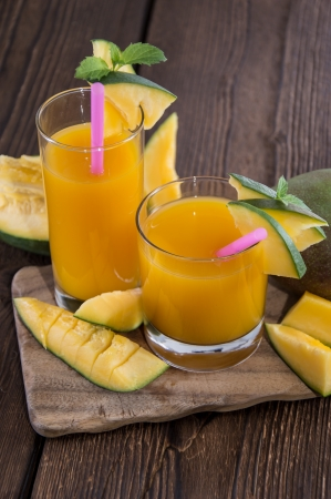 Fresh made Mango Juice with fruits on wooden background photo