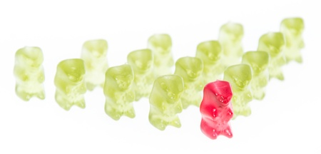 Red Gummi Bear is leading the group (isolated on white) photo