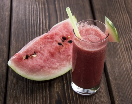 Homemade Watermelon Juice with fresh fruit pieces on wood photo