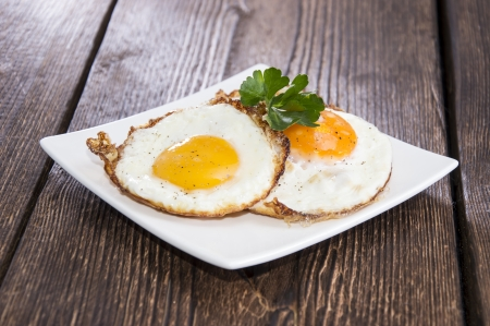 huevos fritos: Huevos fritos en un plato (fondo de madera)