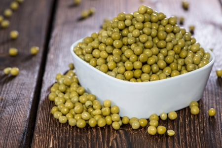 canned peas: Bowl filled with canned Peas on wooden background