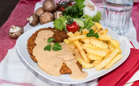 Portion of Wiener Schnitzel with Chips and Sauce photo