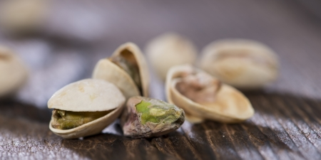 Pistachios on wooden background (macro shot) photo