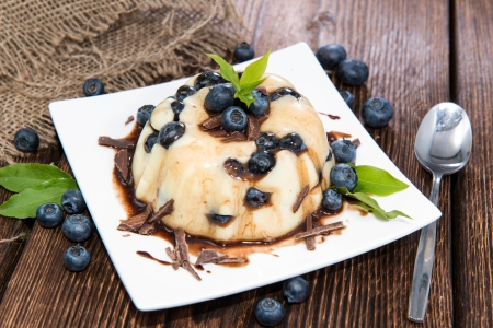 Pudding Dessert with Chocolate Sauce and fresh Berries on wooden background photo