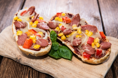 Pizza Baguette with Salami Slices on wooden background photo
