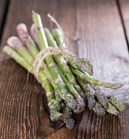 Bunch of Green Asparagus on wooden background photo