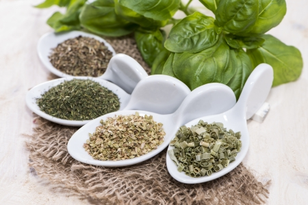 Small portions of fresh Herbs (macro shot on white wooden background) photo