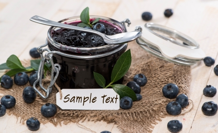Portion of fresh made Blueberry Jam with fruits and a small label photo