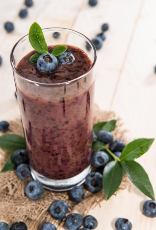 Blueberry juice with fresh fruits on wood photo