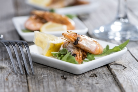 Portion of fried Prawns on vintage wooden background photo