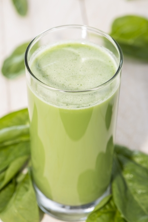 vegetable gardening: Spinach Juice on wooden background (macro shot)