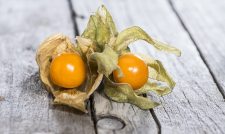 Fresh Physalis Fruits on vintage wooden background photo