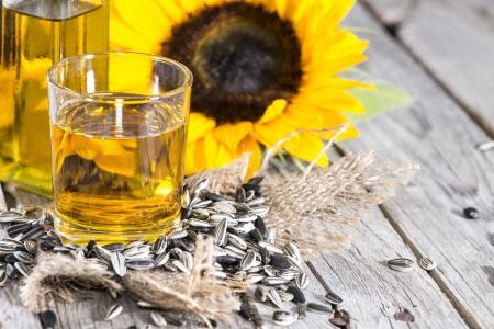 Zonnebloemolie met zaden op vintage houten achtergrond Stockfoto