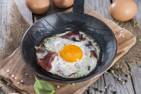 Fried Egg in a vintage Pan on wooden background photo