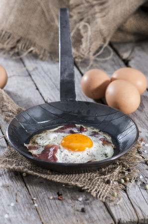 Fried Egg in a small Pan on vintage wooden background photo