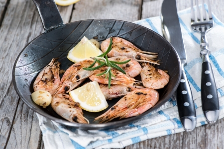 Shrimps with garlich and herbs in a skillet photo
