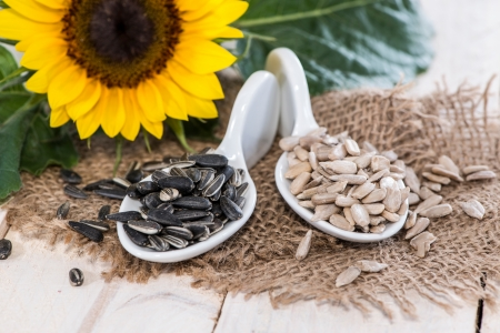 Portion of Sunflower Seeds on wooden background photo