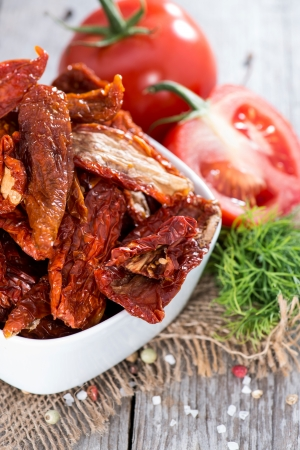 Portion of dried and salted Tomatoes on wooden background photo