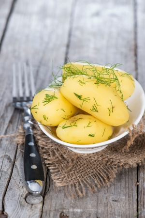 Heap of fresh Potatoes with herbs on wooden background photo