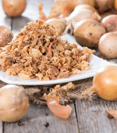 Portion of fresh Fried Onions on wooden background photo