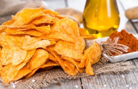 Potato Chips with Paprika Powder on vintage wooden background
