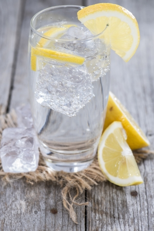 Sparkling Water with Lemon and ice on wooden background photo