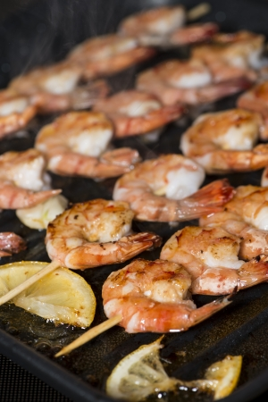 Fresh skewered Prawns in a Skillet (close-up shot) photo