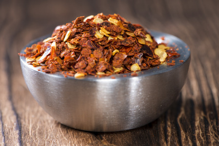 Chilli Spice in a small Bowl on dark wooden background