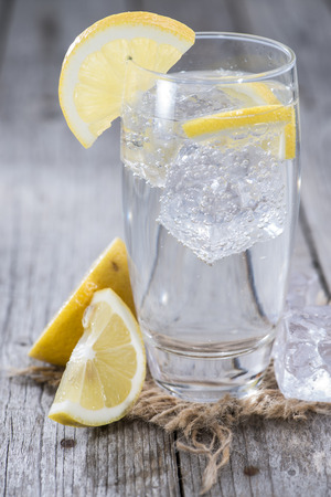 sparkling water: Sparkling Water with Lemon and ice on wooden background Stock Photo