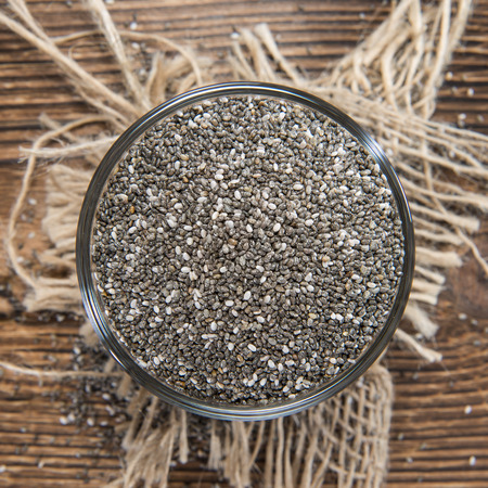 chien: Chia Seeds in a small bowl (on dark wooden background)