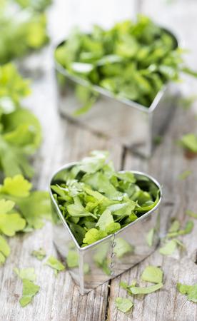Fresh flat leaf Parsley (close-up shot) on weathered wooden background photo