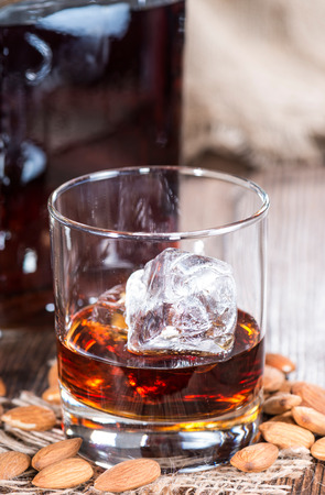 amaretto: Glass with Amaretto and ice cubes on dark with some almonds Stock Photo