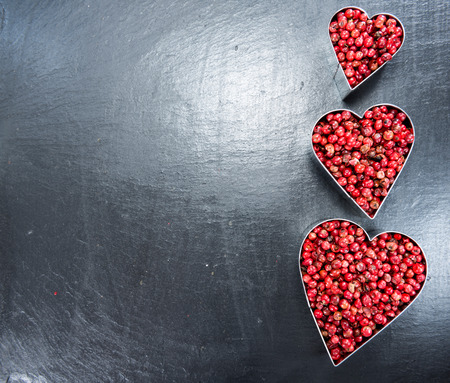 Heart shape with Pink Peppercorns on dark background (I Love Herbs Concept) photo