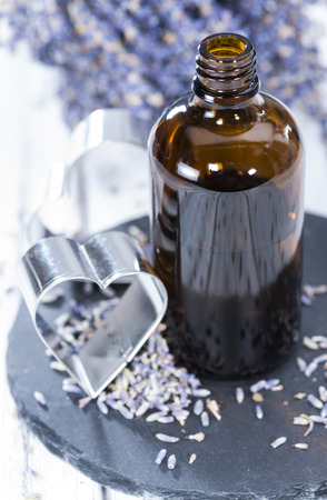 Lavender Oil in a small bottle on bright background photo