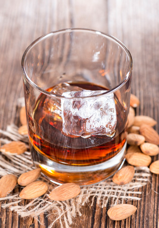 amaretto: Glass with Amaretto and ice cubes on dark background with some almonds Stock Photo