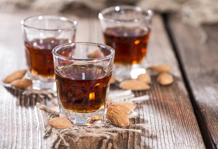 amaretto: Amaretto Shot on dark wooden background with some almonds