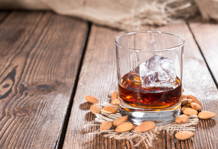 Glass with Amaretto and ice cubes on dark background with some almonds Stock Photo