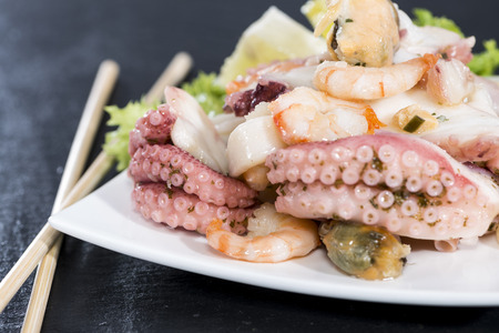 Portion of Seafood Salad (close-up shot) with squid, mussels and prawns photo