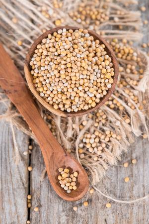 Portion of Mustard Seeds on vintage wooden background photo