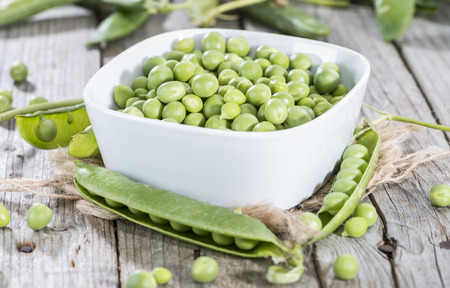 Portion of fresh harvested Peas on wooden background