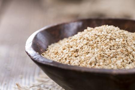 Portion of Sesame Seeds on dark wooden background (close-up shot)