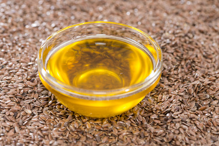 linseed oil: Small portion of golden Linseed Oil with some seeds (close-up shot) Stock Photo
