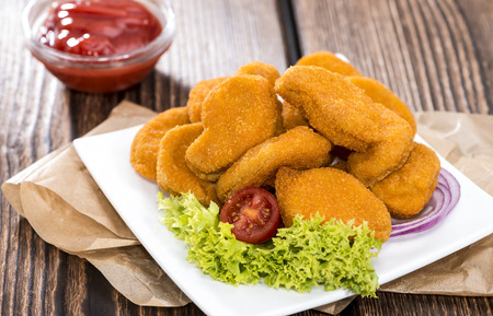 Portion of fresh made crispy chicken nuggets with tomato ketchup
