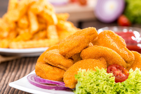 Some fresh made golden Chicken Nuggets with crispy chips