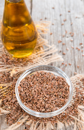 common flax: Bowl with Linseeds (close-up shot) on vintage wooden background Stock Photo
