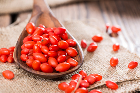 Some fresh Goji Berries (also known as Wolfberry) on vintage wooden background photo
